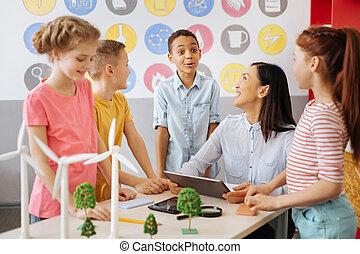 Happy schoolchildren joking with their ecology teacher