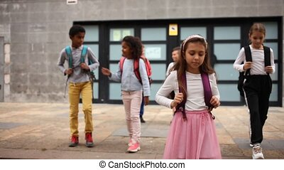 Team of positive schoolchildren running in race in the street and laughing outdoors