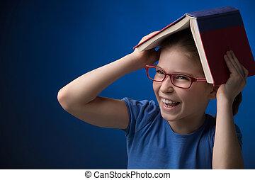 Happy schoolgirl. Happy little girl in glasses carrying a...