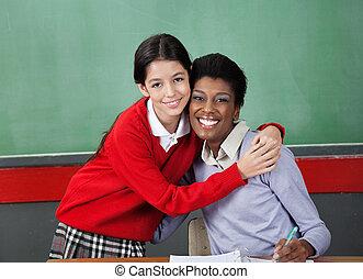 Happy Schoolgirl Hugging Professor In Classroom