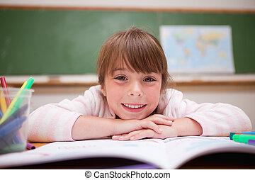 Happy schoolgirl leaning on a desk