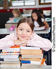 Happy Schoolgirl Leaning On Stacked Books At Desk