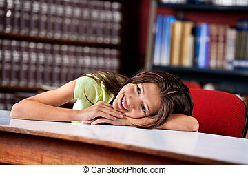 Happy Schoolgirl Looking Away While Leaning On Table