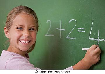 Happy schoolgirl writing a number on a blackboard