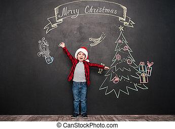 Happy screaming child standing near Christmas drawing on blackboard