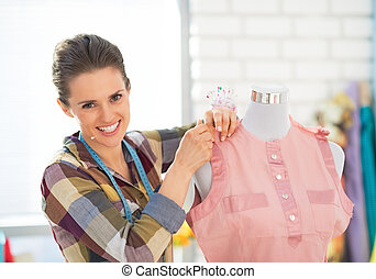 Happy seamstress adjusting clothing on mannequin