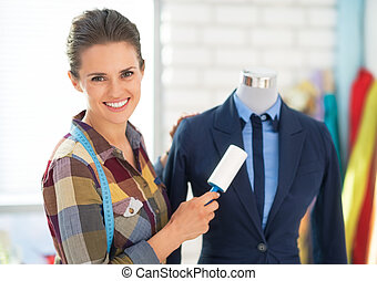 Happy seamstress cleaning suit on mannequin