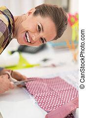 Happy seamstress cutting fabric