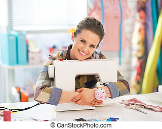 Happy seamstress embracing sewing machine