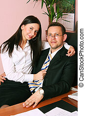 happy secretary and businessman sitting in the office chair