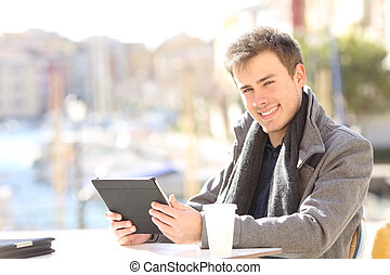 Happy self employed holding tablet looking at you
