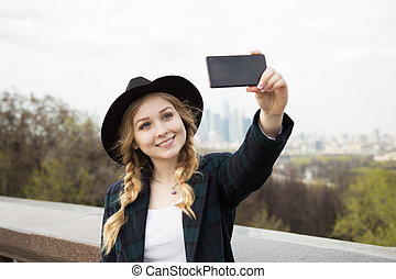 Attractive girl doing mobile phone photography for social media.