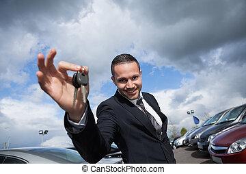 Happy seller holding car keys outdoors