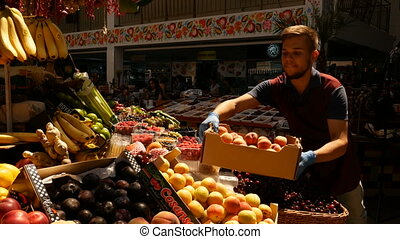 Happy seller with peaches near the counte