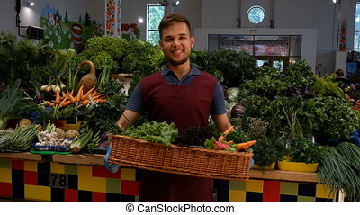 Happy seller with vegetables near the counter