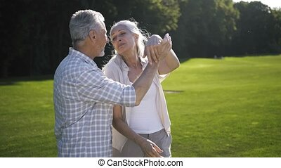 Happy senior aged couple dancing outdoors on lawn