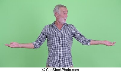 Happy senior bearded man comparing something - Studio shot...