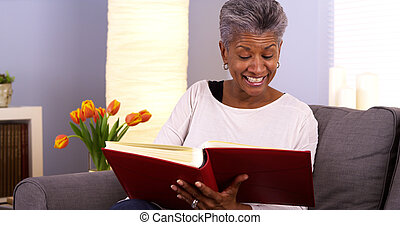 Happy senior black woman looking though photo album