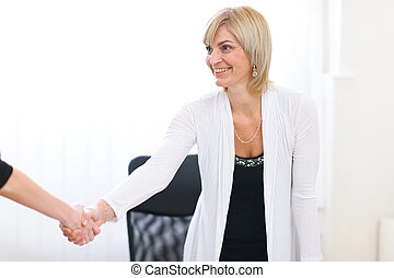 Happy senior business woman greeting visitor at office