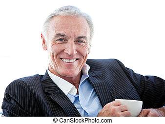 Happy senior businessman drinking a coffee