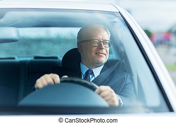 happy senior businessman driving car