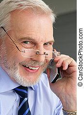 Happy senior businessman making a phone call