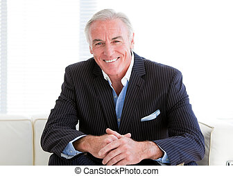 Happy senior businessman sitting on a sofa