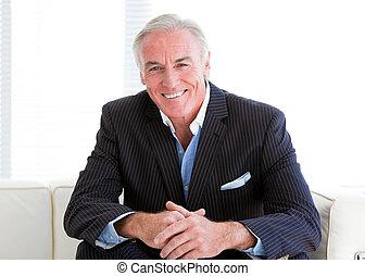 Happy senior businessman sitting on a sofa