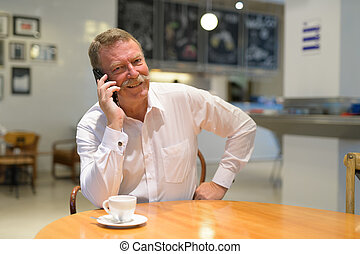 Happy senior businessman sitting while talking on phone at the coffee shop