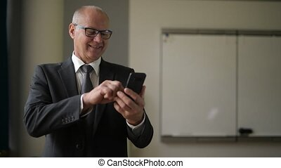 Happy Senior Businessman Thinking While Using Phone By The...