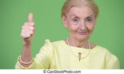 Happy senior businesswoman giving thumbs up