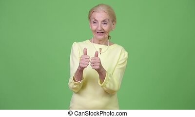 Happy senior businesswoman giving two thumbs up