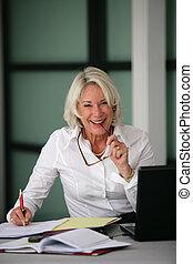 happy senior businesswoman working at her desk