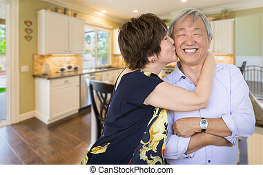 Happy Senior Chinese Couple Kissing Inside Beautiful Custom Kitchen.