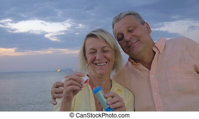 Happy senior couple blowing bubbles on the beach