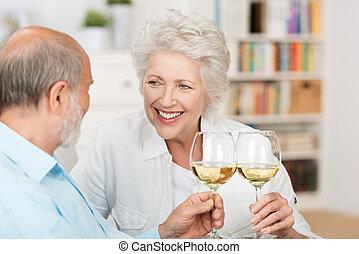 Happy senior couple celebrating clinking their glasses of...