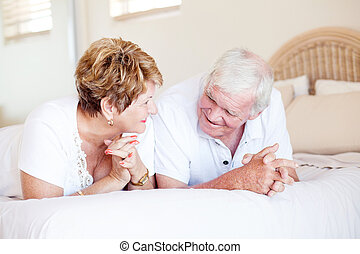 happy senior couple chatting on bed