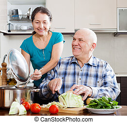 happy senior couple cooking with vegetables