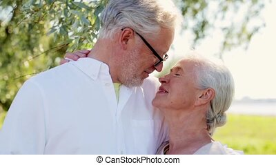 happy senior couple cuddling at summer park - old age, love...
