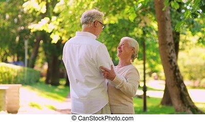 happy senior couple dancing at summer city park