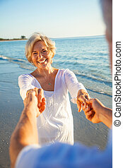 Happy Senior Couple Dancing Holding Hands on Sunset Beach