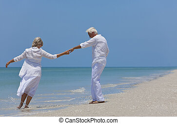 Happy Senior Couple Dancing Holding Hands on A Tropical...