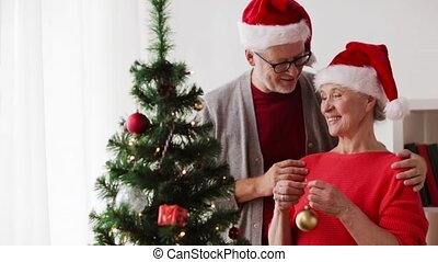 happy senior couple decorating christmas tree