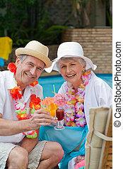 Happy senior couple drinking cockta