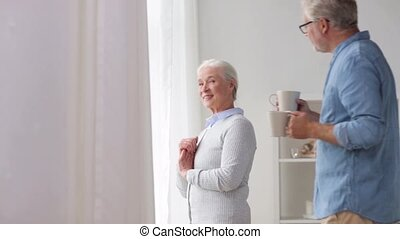 happy senior couple drinking coffee at home
