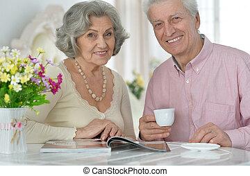 Senior couple drinking tea  and reading magazine