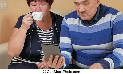 Happy senior couple enthusiastically looking at screen tablet computer with a cup of tea. Husband and wife are discussing what they saw