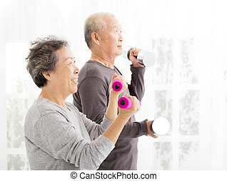 happy senior couple exercising with dumbbells
