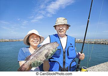 happy senior couple go fishing and showing big fish