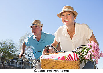 Happy senior couple going for a bike ride in the city on a...